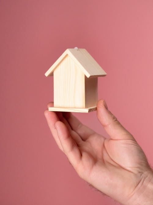 Person Holding White Wooden House Miniature
