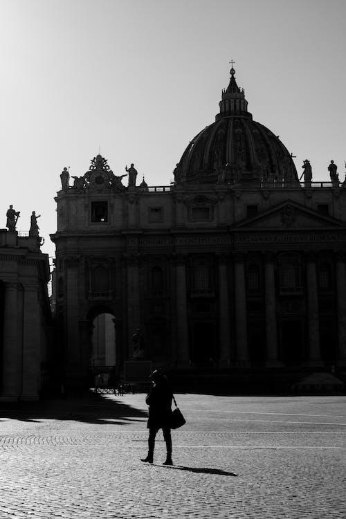 Unrecognizable citizen walking on square against St Peters Basilica