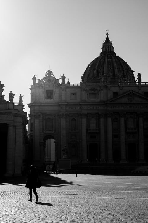Black and white back view of anonymous person walking on square against Saint Peters Basilica with statues in Vatican City