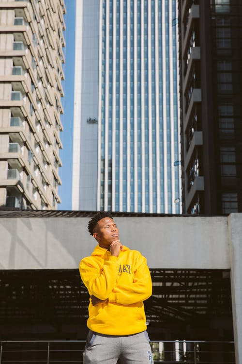 Man in Yellow Hoodie Standing Near White Concrete Building
