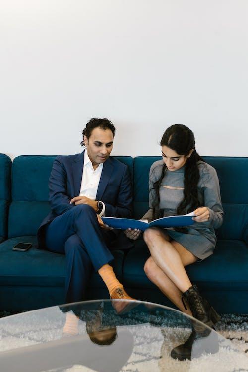 Man in Blue Suit Sitting Beside Woman in Blue Blazer