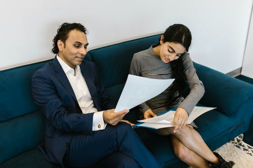 Man in Blue Suit Jacket Sitting Beside Woman in Black Long Sleeve Shirt Reading Book