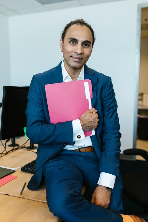 Man in Blue Suit Holding a Folder
