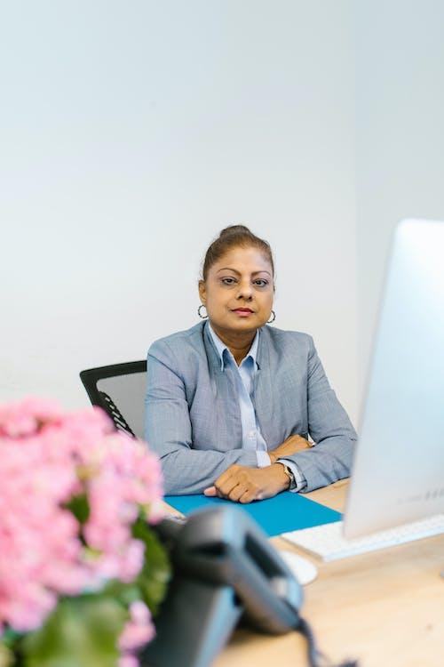 Woman in Blue Blazer Sitting on Black Chair