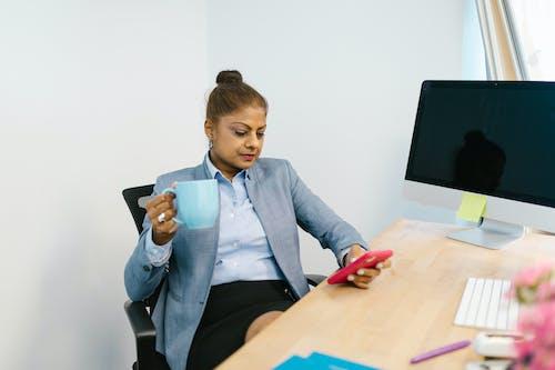 Woman Holding a Blue Ceramic Mug while Texting