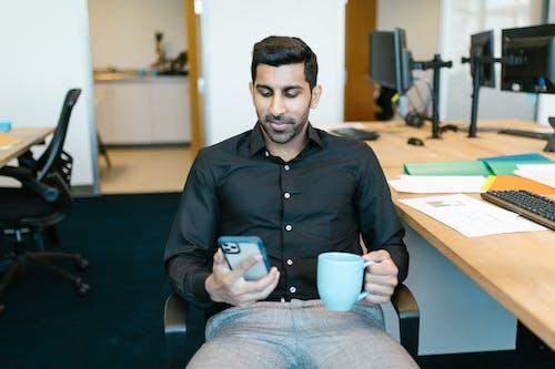 Man in Black Dress Shirt Holding Blue Ceramic Mug