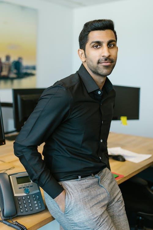Man in Black Dress Shirt Leaning on a Desk