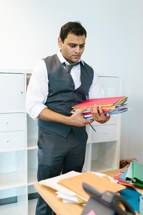 Man Wearing Waistcoat Carrying Folders