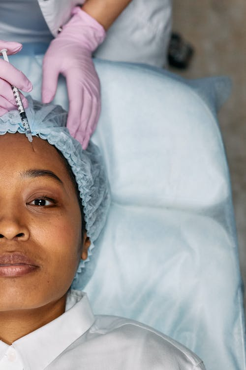Woman Lying Down Receives Forehead Botox