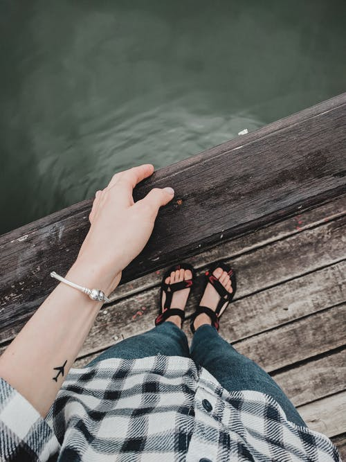 Person in Blue Denim Jeans and Black Leather Sandals Sitting on Wooden Dock