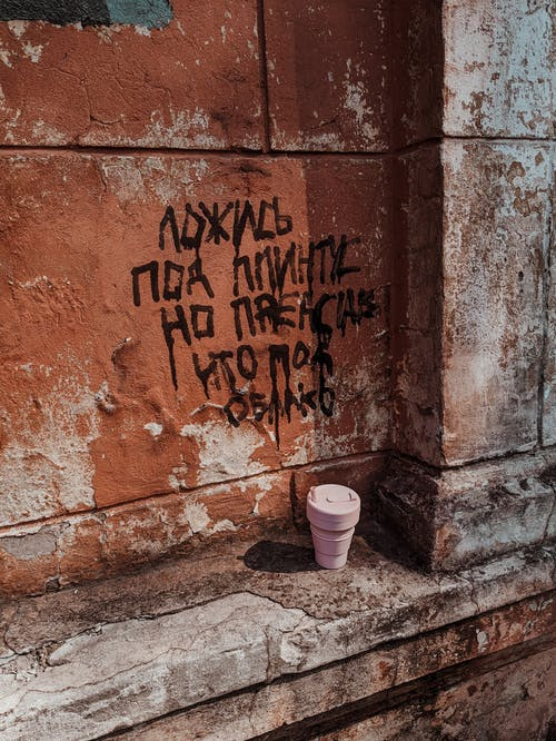 White and Pink Plastic Cups Beside Brown Concrete Wall