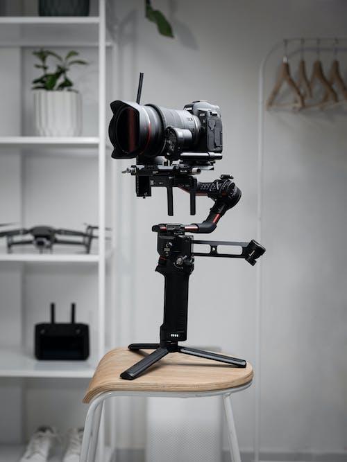 Black Dslr Camera on Brown Wooden Seat