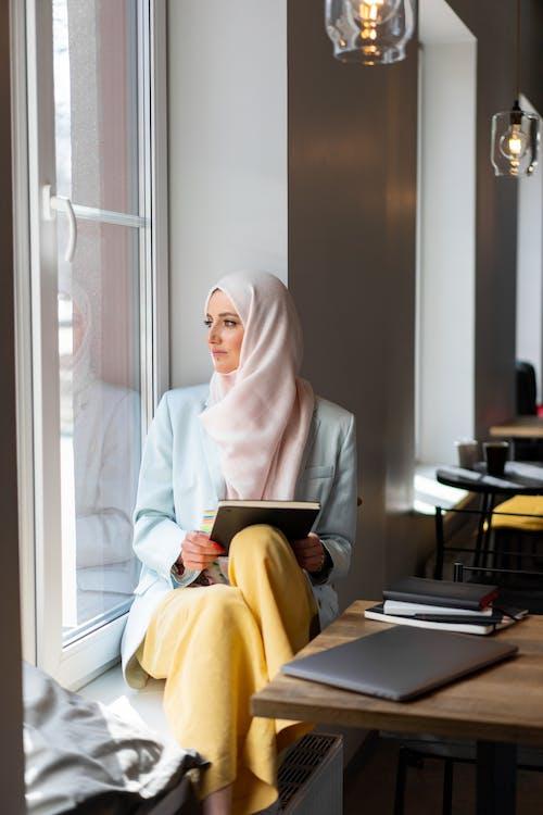 Женщина в белом хиджабе сидит на стуле