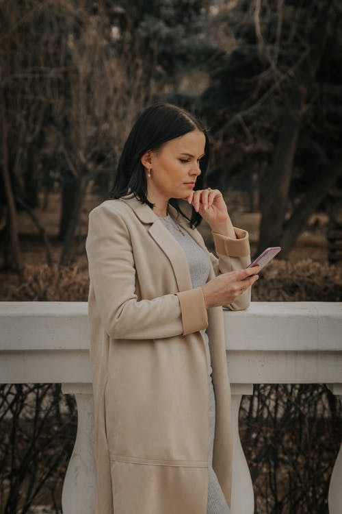 Side view of peaceful female in coat using mobile phone while standing in park in fall on cloudy day