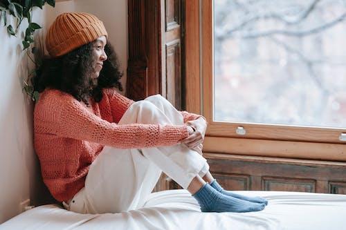 Positive African American woman in hat near window