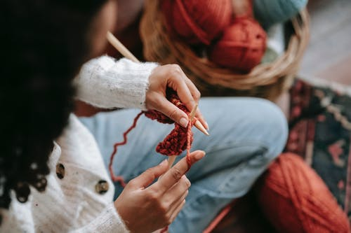 Unrecognizable woman knitting with threads