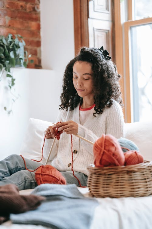 Focused African American female with black hair knitting with needles while sitting near window on bed with threads in room