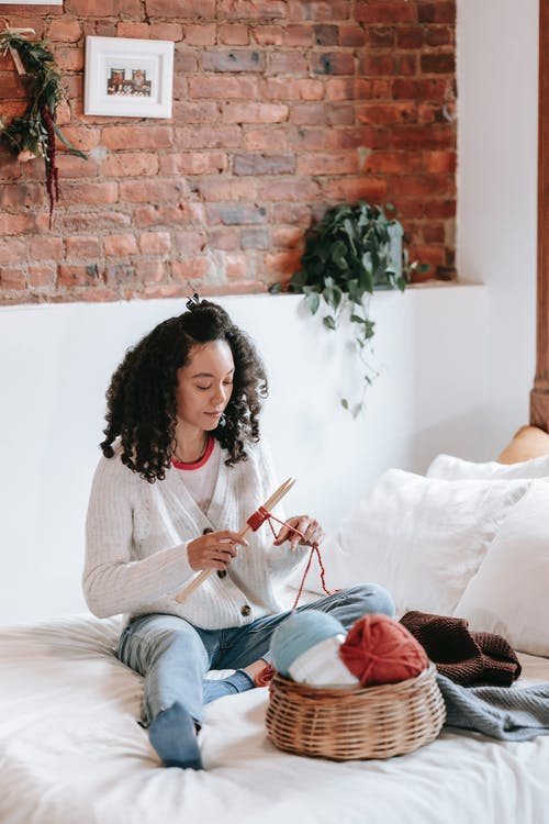 Calm young ethnic woman knitting warm clothes on bed
