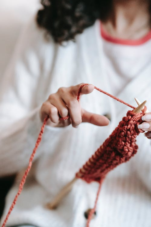 Crop anonymous with curly dark hair tying woolen thread on finger while knitting with yarn and needles at home