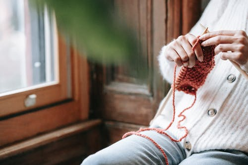 Crop anonymous lady sitting near window and knitting during weekend at home