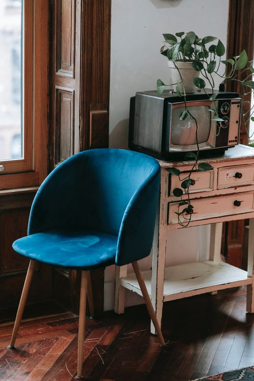 Comfortable soft chair and old wooden cabinet with vintage TV set placed near window in retro styled apartment