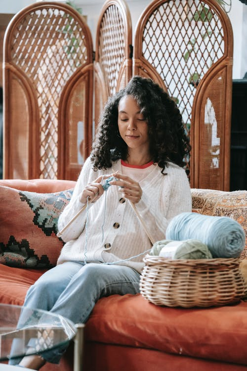 Young ethnic female millennial knitting with yarn and needles on sofa in cozy apartment