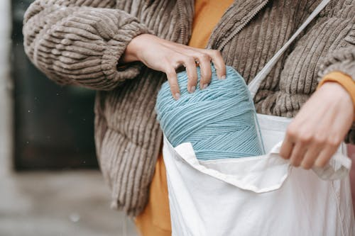 Crop female artisan in warm clothes putting skein in eco friendly bag on street in daylight