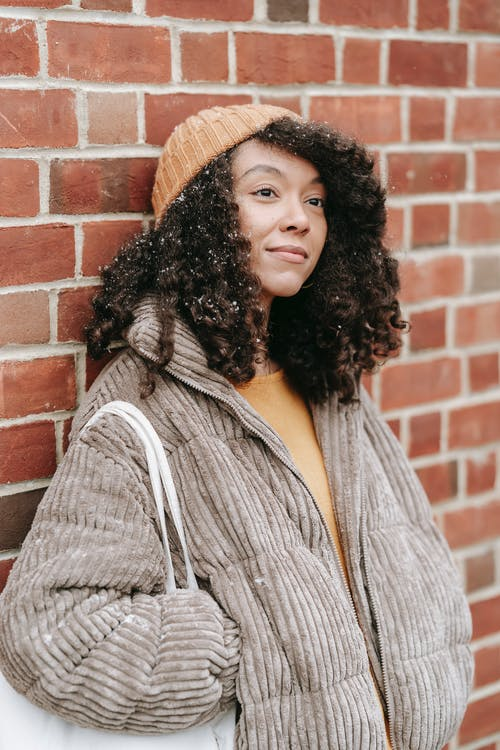 Dreamy young black female in warm clothes with hand in pocket looking away on winter street