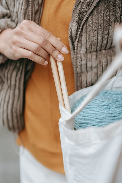 Crop artisan with knitting needles in eco bag