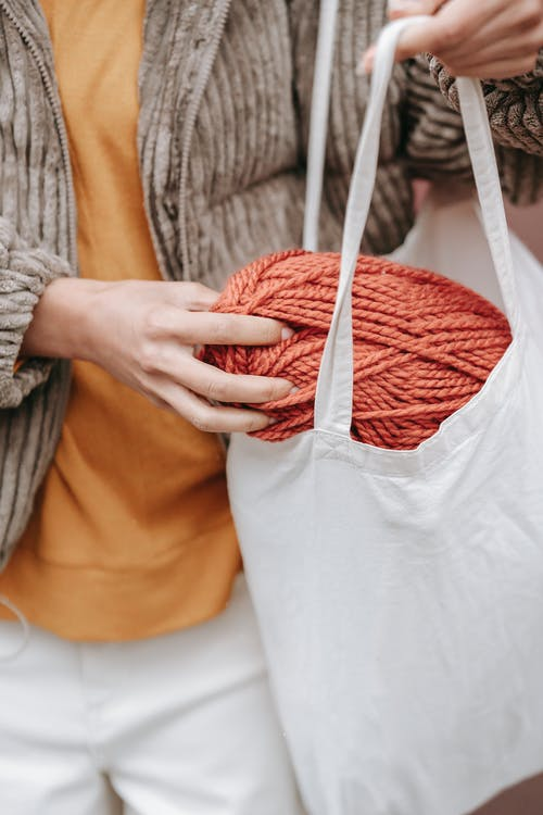 Crop craftswoman putting skein in eco bag