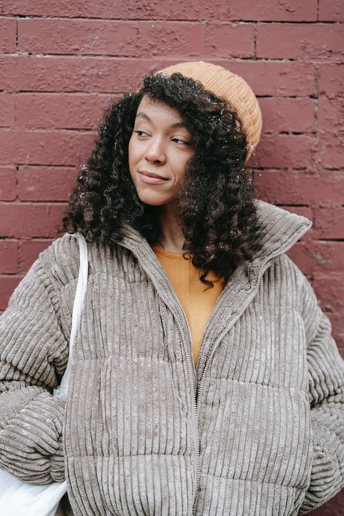 Dreamy young black female with curly hair in warm clothes standing with hands in pockets while looking away on street