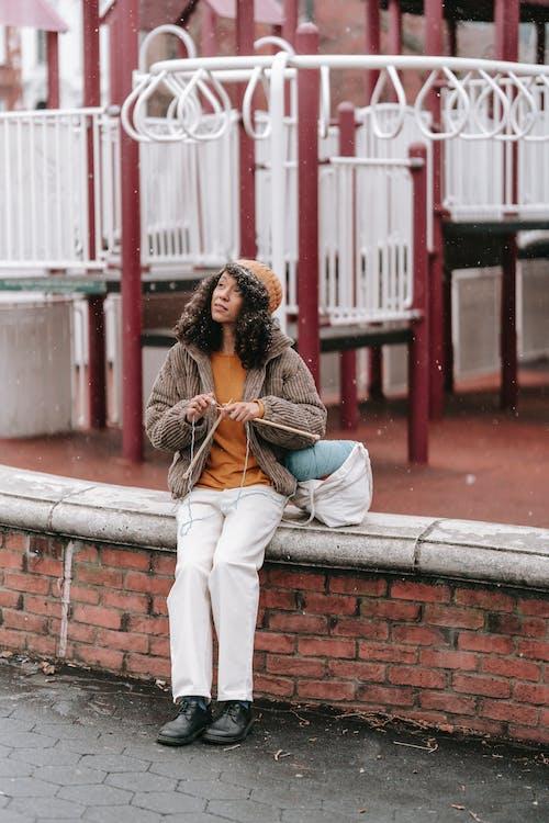 Black craftswoman with yarn knitting on urban bench