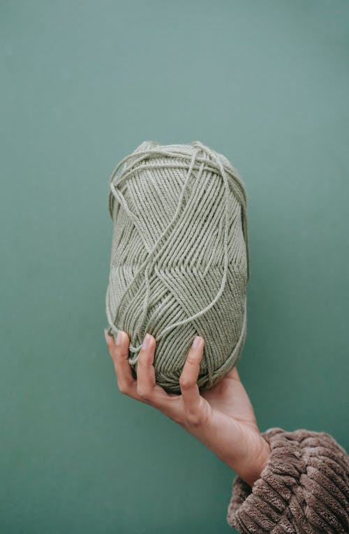 Crop unrecognizable female reaching out hand and demonstrating ball of yarn against green background