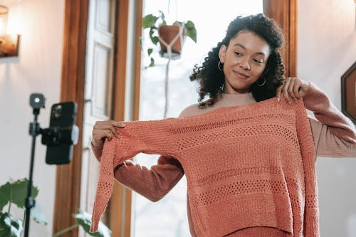 Smiling ethnic woman trying on sweater and filming video