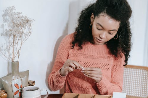 Concentrated ethnic female with curly hair sitting on chair and creating handmade accessory on thread