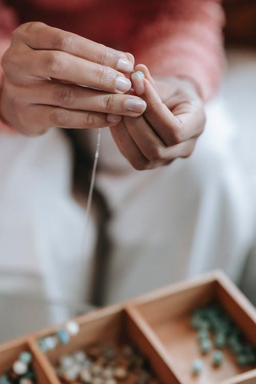 Ethnic female artisan creating handmade accessory