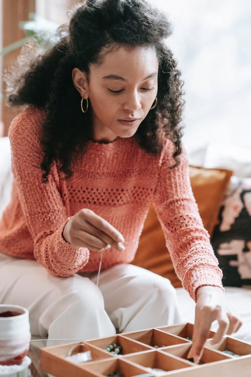 Serious ethnic curly haired female sitting at table and creating handmade bijouterie at home