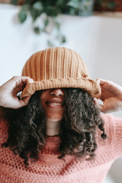 Anonymous African American female with curly black hair pulling knitted hat on eyes while standing in light room at home