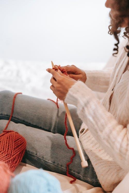 Crop black artisan knitting on bed at home