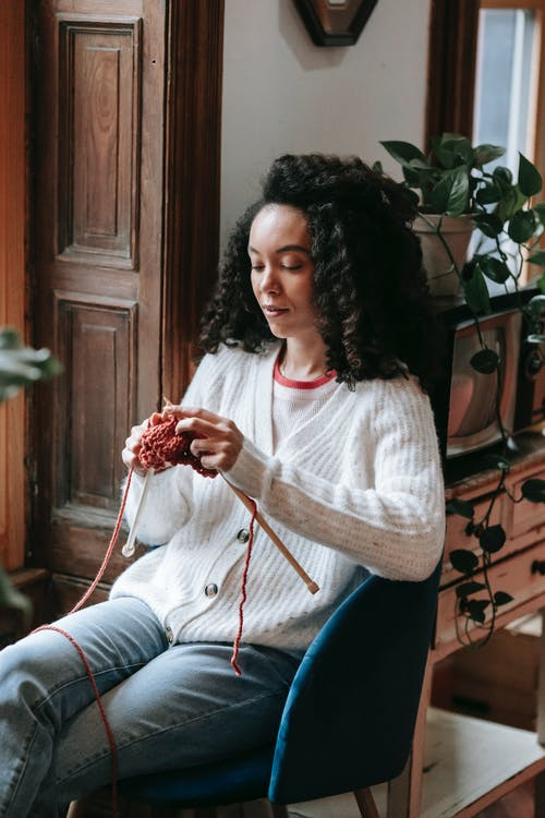 Attentive young African American craftswoman with curly hair and yarn knitting with needles in light house room