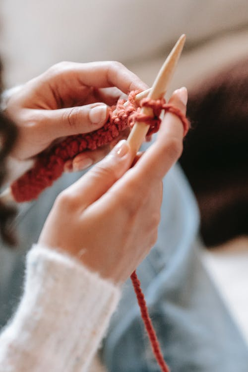 High angle of crop anonymous female artisan with needles and yarn knitting in house room on blurred background