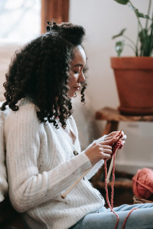 Black artisan with curly hair knitting at home