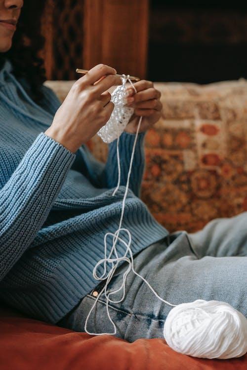Crop black artisan crocheting on sofa at home