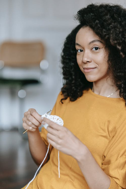 Charming African American craftswoman with hook and yarn looking at camera while crocheting in house