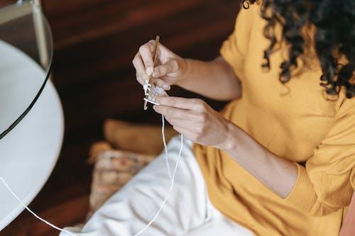 Crop artisan crocheting on sofa at home