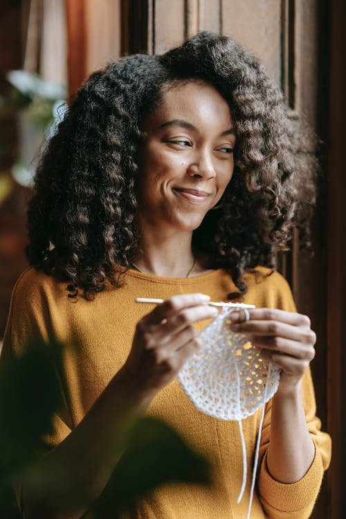 Cheerful young African American craftswoman with hook and yarn crocheting while looking away at home