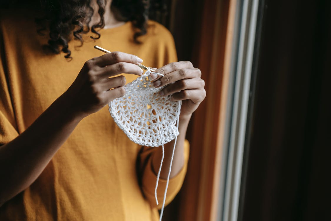 Crop craftswoman with hook crocheting at home