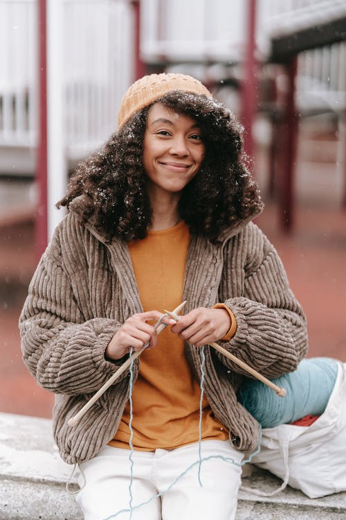 Positive African American woman with dark lush hair wearing orange pullover and beige jacket and white jeans hat doing needlework