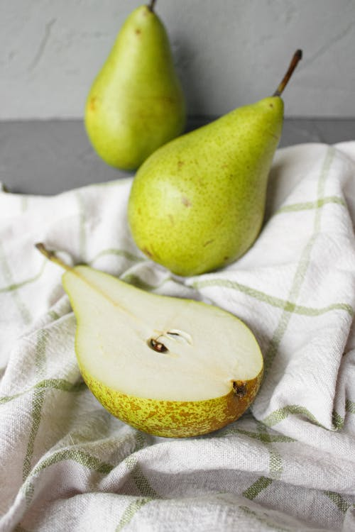 Green pears placed on cloth on table