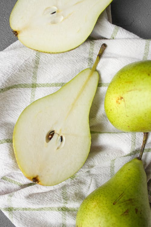 From above of fresh ripe pieces of green pears placed on white fabric on table in light place